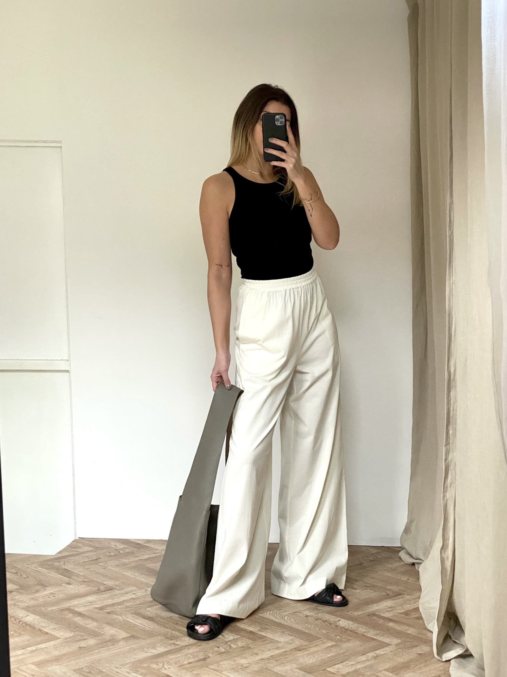Emma Hill wears black racer back vest, white wide leg jersey trousers, slouchy grey leather hobo bag, black chunky sandals. Casual chic Summer outfit