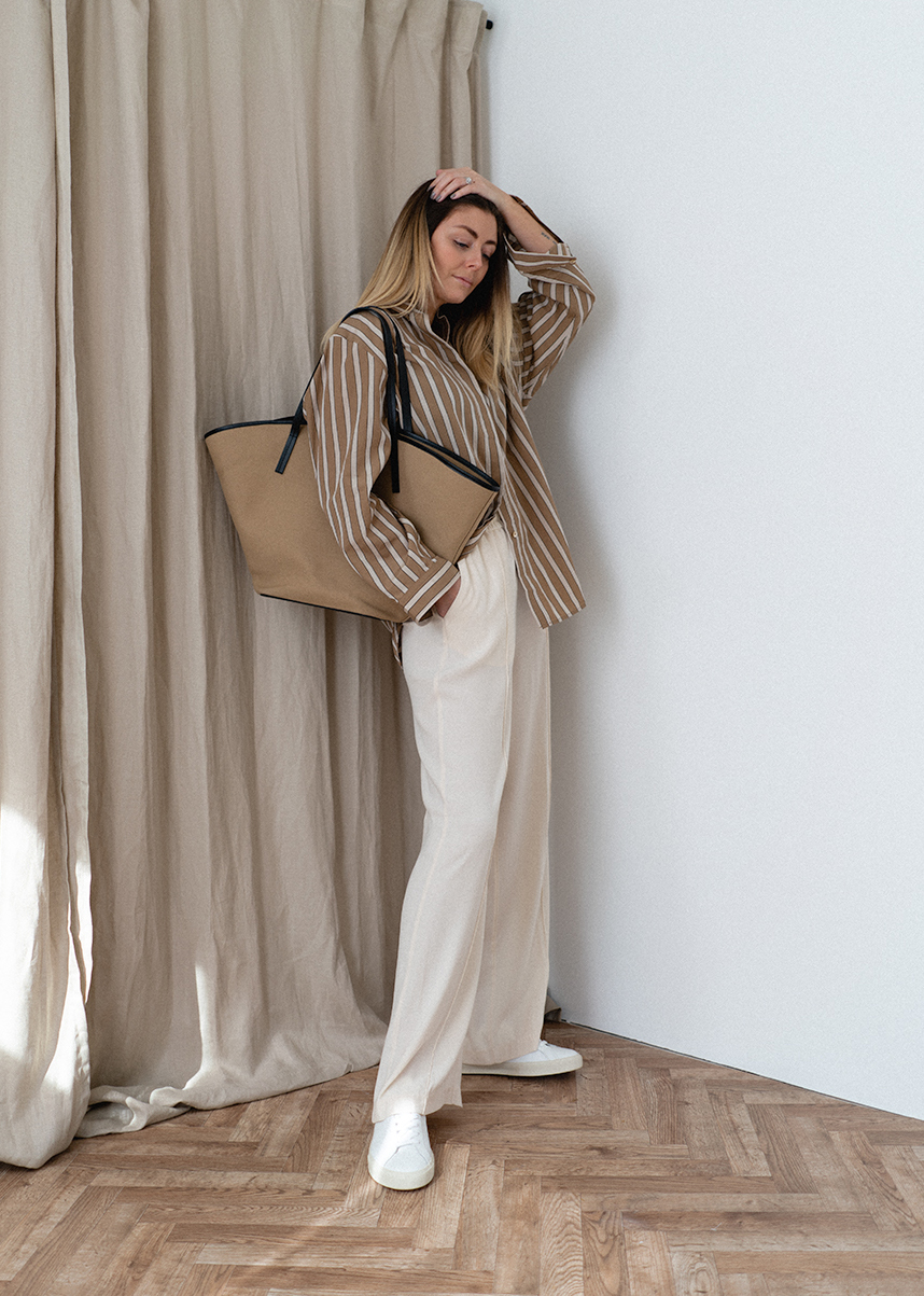 Emma Hill wears brown and white stripe oversized shirt, white wide leg trousers, white trainers, neutral canvas tote bag. Chic causal Spring Summer outfit