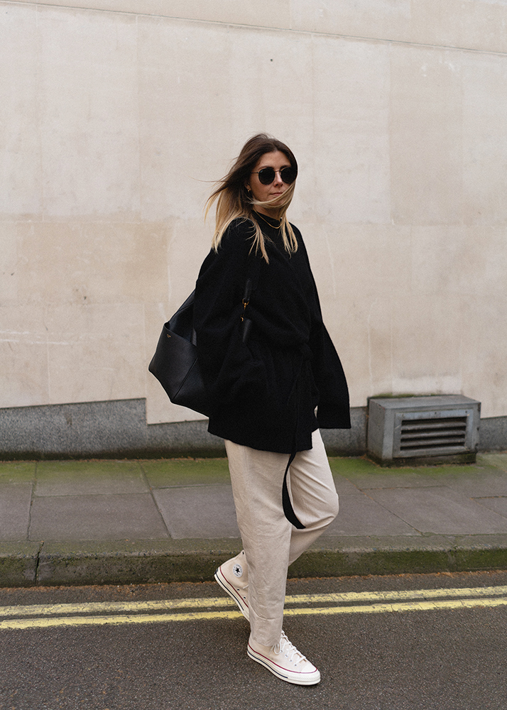 Emma Hill black oversized cashmere Raey cardigan, beige chino trousers, parchment Converse Chuck 70's