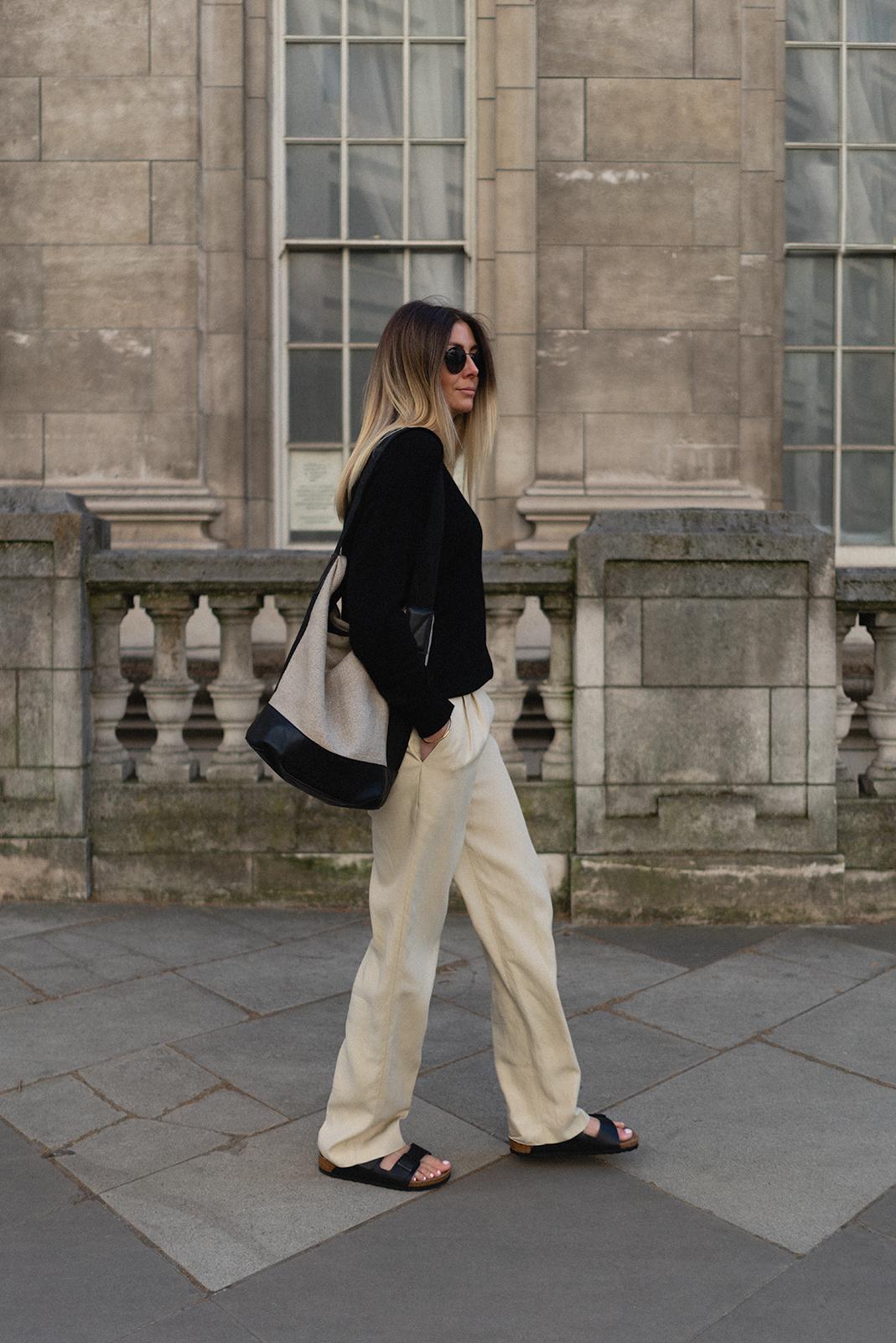 Emma Hill wearing black sweater, linen bucket bag, beige wide leg trousers, black leather Birkenstocks. How to style Birkenstocks for Spring and Autumn