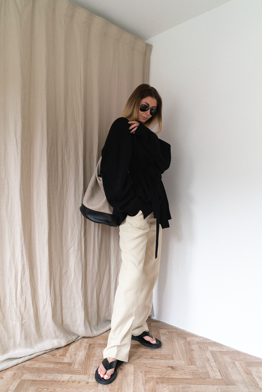 Emma Hill wears black cardigan, Loulou Studios Takaroa straight leg creased trousers, black sandals, linen canvas bucket bag. Chic casual Spring outfit