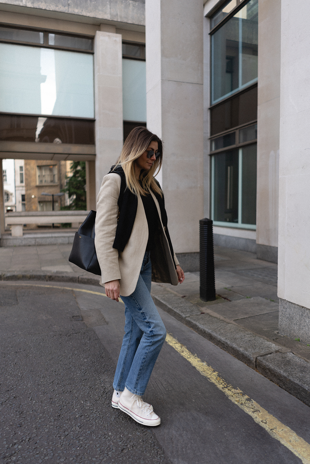 Emma Hill wears black jumper over shoulders, beige linen blazer, black leather Celine Seau Sangle bucket bag, straight leg jeans, Converse Chuck 70 in parchment. Casual but chic Spring outfit
