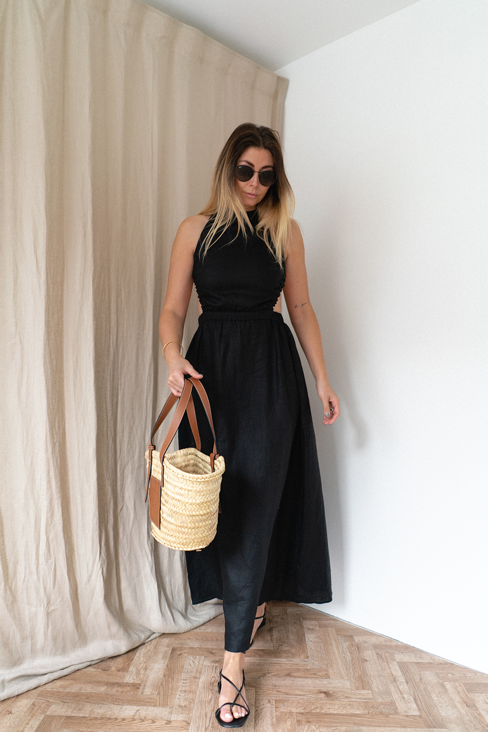 Emma Hill wears black linen backless dress by Sir the label. Loewe basket bag. Black strappy barely there sandals. Chic Summer outfit