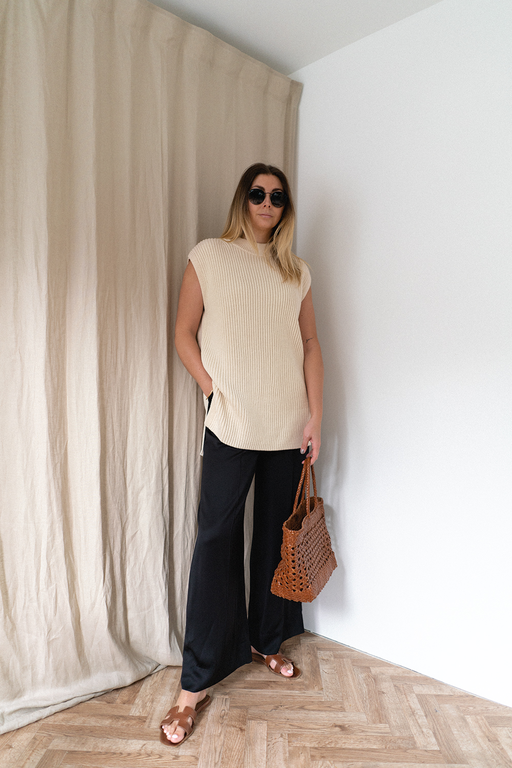Emma Hill wears black wide leg silk trousers, tan Hermes Oran sandals, Dragon Diffusion Cannage woven leather basket bag, cream sleeveless sweater jumper vest. Chic Spring Summer outfit