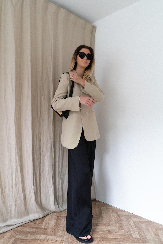 Emma Hill wears linen blazer, Elleme raffia baguette bag, black silk trousers, black thong sandals. Chic Spring Summer outfit