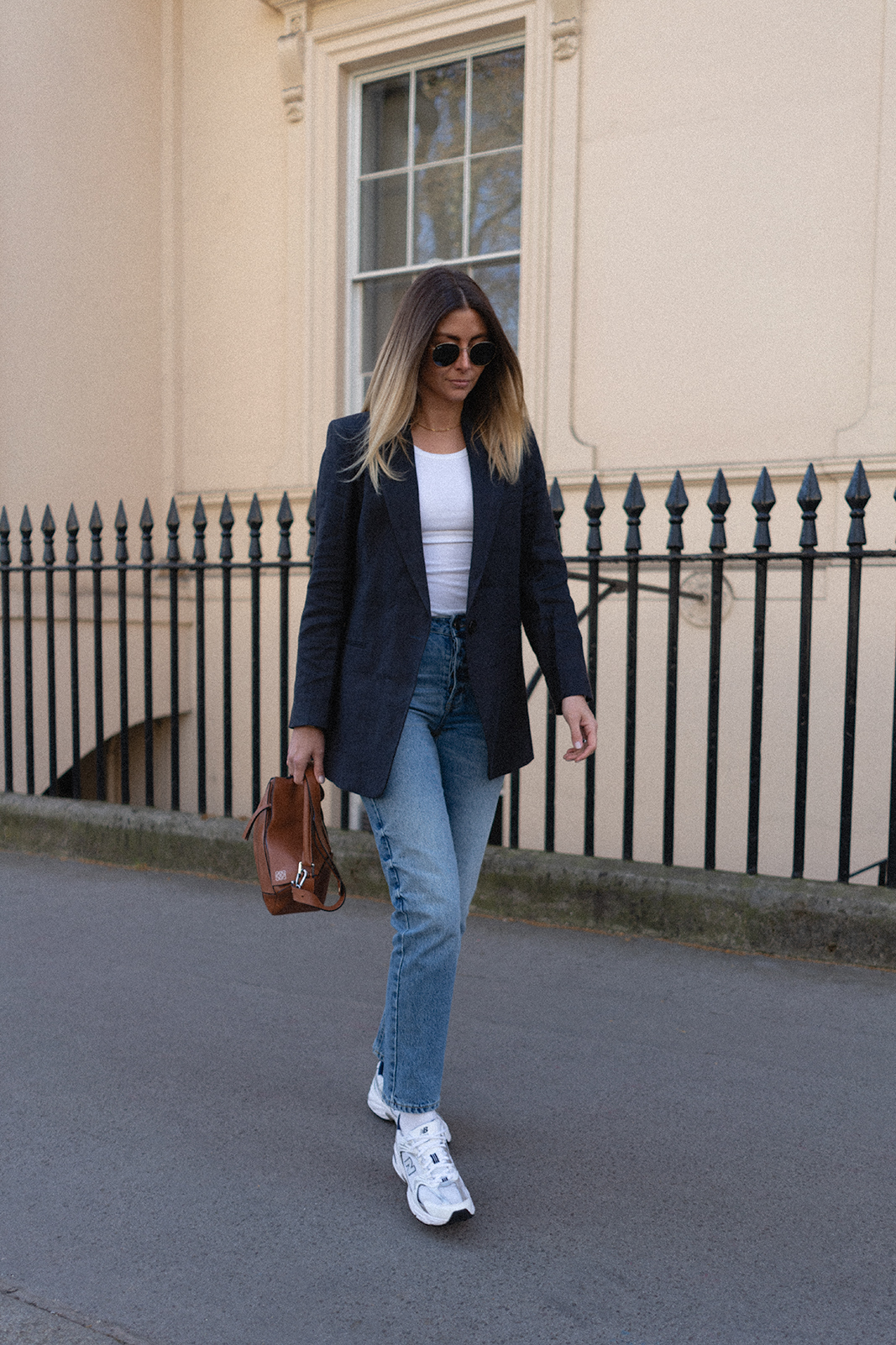 Emma Hill wears navy linen blazer, mid wash straight leg jeans, white tennis socks, New Balance 530 trainers, tan loewe puzzle bag, white vest. Casual Spring Summer outfit