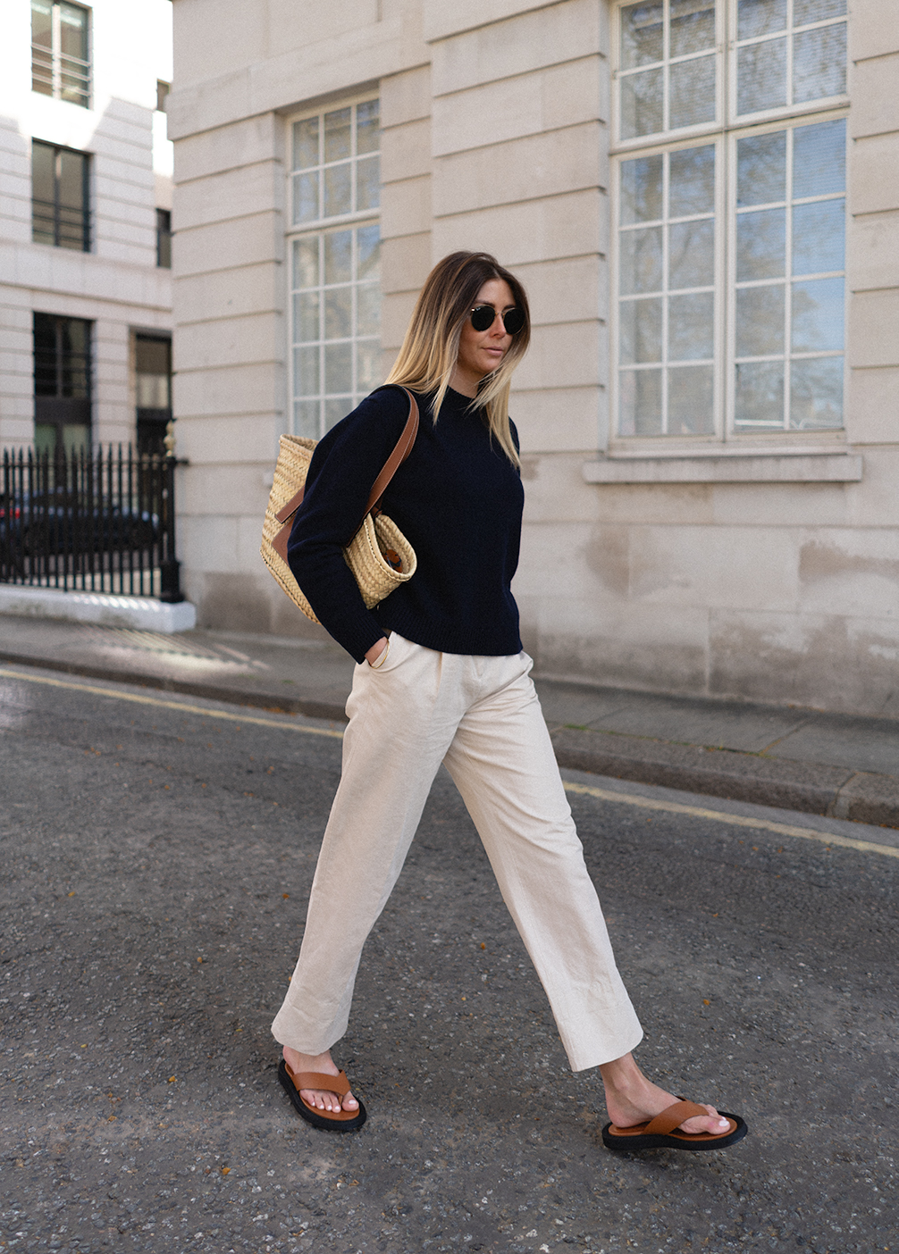 Emma Hill wears navy sweater jumper, beige chino trousers, tan thong sandals, Loewe basket bag. Chic basic Spring outfit