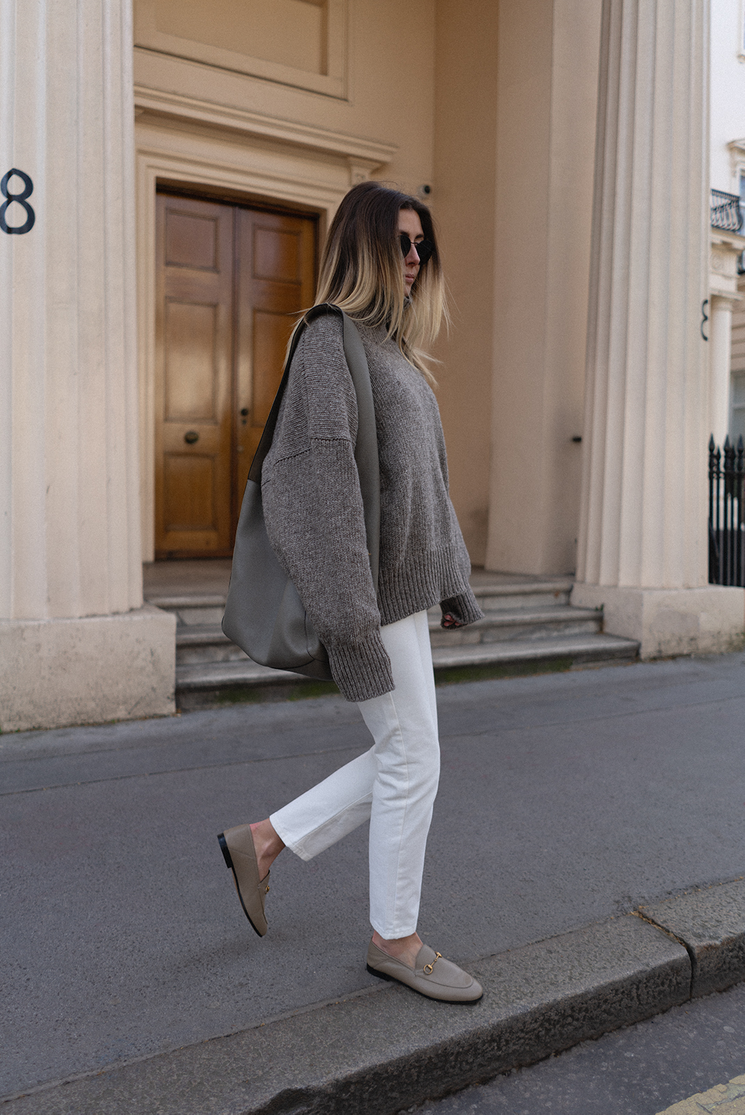 Emma Hill wears taupe chunky knit jumper, white Raey straight leg jeans, taupe beige Gucci brixton loafers, grey Joseph XL slouch hobo bag. Cosy Spring outfit