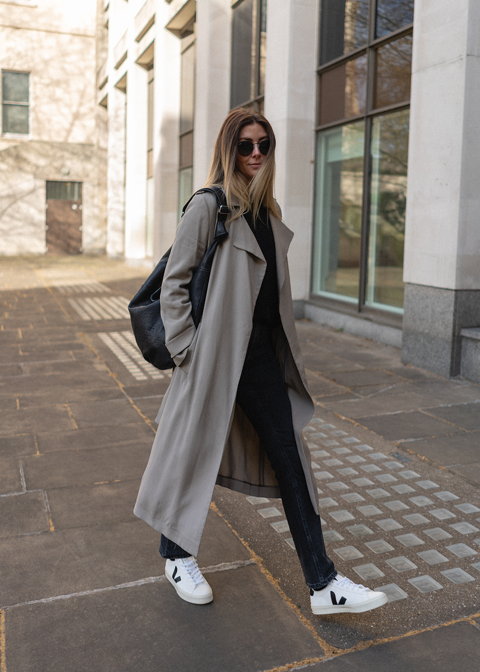 Emma Hill wears taupe trench coat, black straight leg jeans, Veja Campo trainers, black croissant slouchy hobo bag. Chic Spring outfit