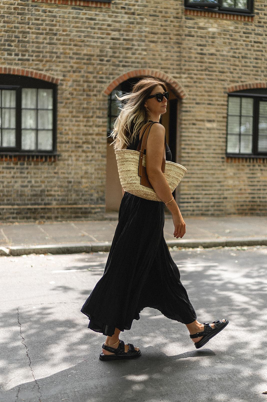 Emma Hill wears Loewe basket bag, black ribbed vest top, black crinkle silk midi skirt, black quilted leather Chanel dad sandals, Celine cat eye Baby Audrey sunglasses. Chic black Summer outfit