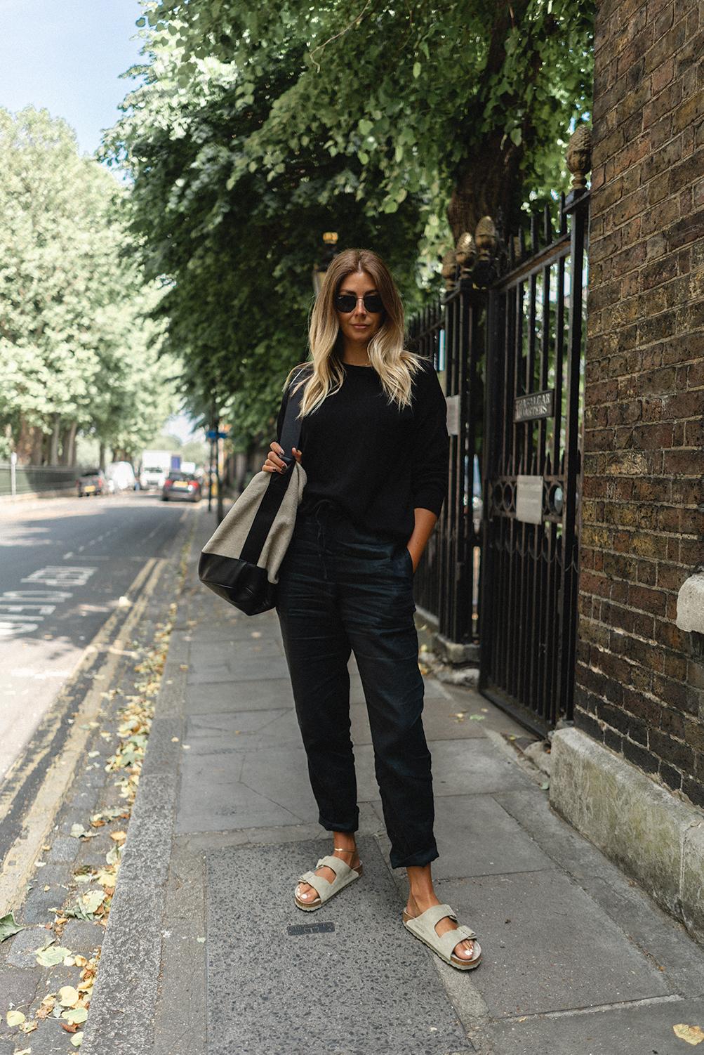 Emma Hill wears all black outfit. Black jumper, black linen trousers, linen camvas bucket bag, faded khaki green suede Birkinstock Arizona sandals. Casual chic Summer outfit