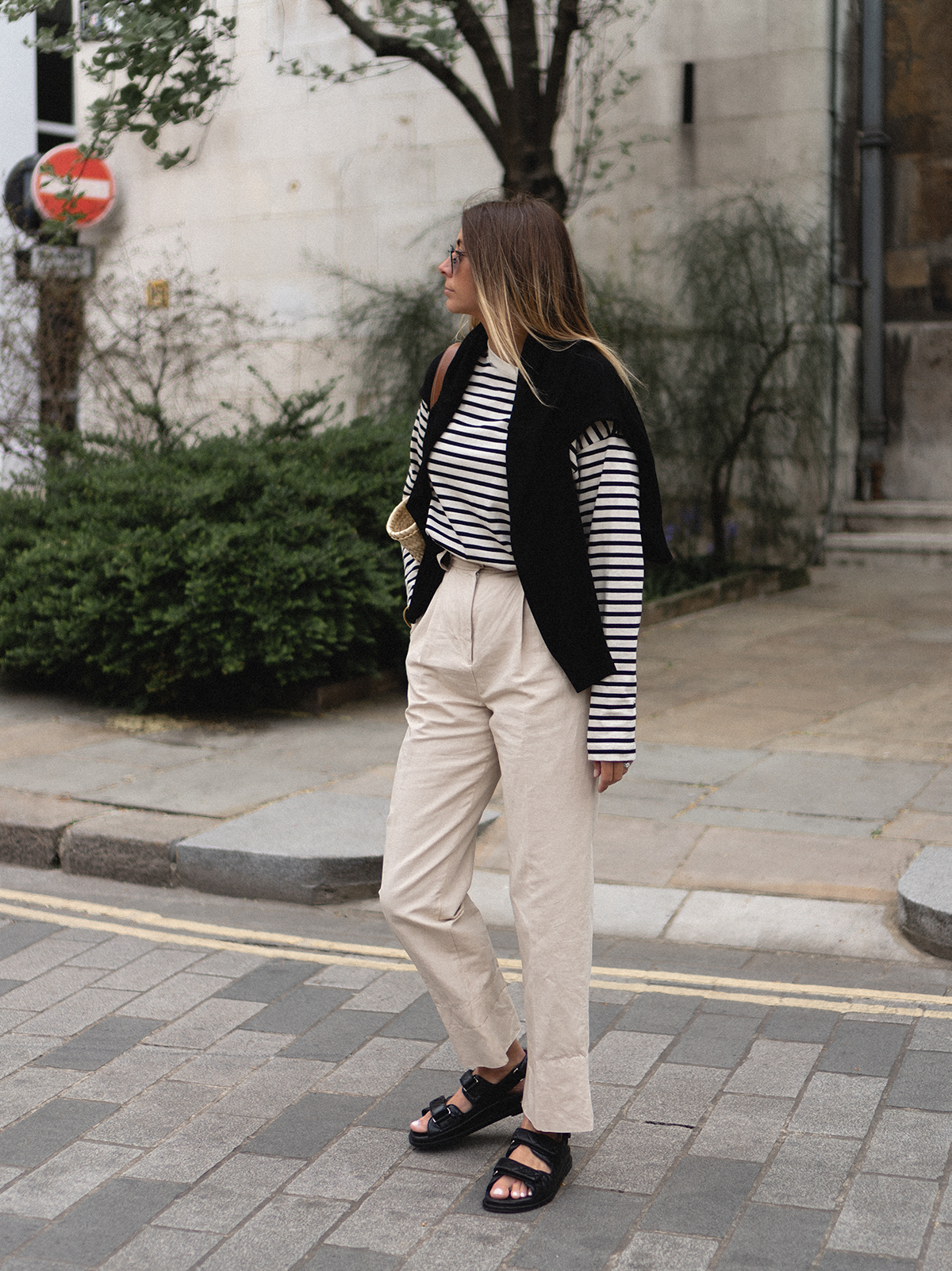 Emma Hill wears black and white breton stripe long sleeve t-shirt, black jumper worn over shoulders, Loewe basket bag, beige high waisted trousers, Chanel quilted leather dad sandals. Chic Spring outfit