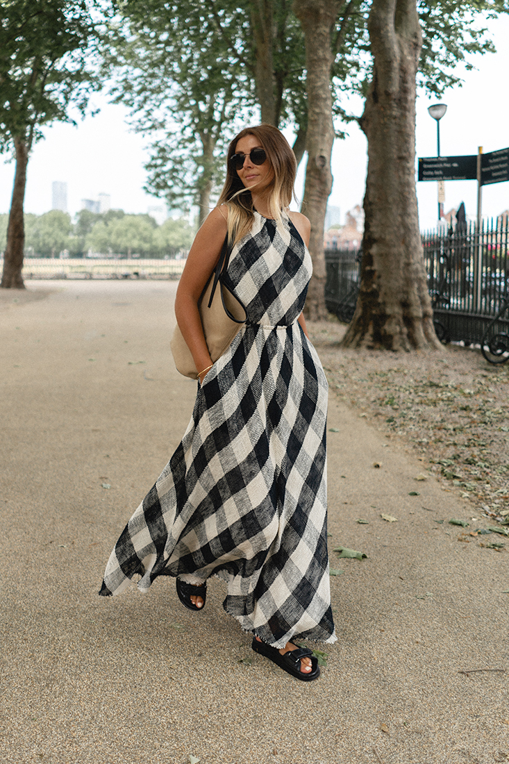 Emma Hill wears black and white check halter dress by Raey, neutral canvas tote bag, Chanel black quilted leather dad sandals. Chic monochrome Summer outfit