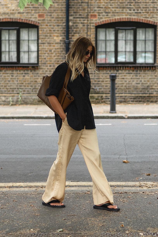 Emma Hill wears black cotton oversized shirt, yellow wide leg trousers, Celine Tri-Fold bag, Dear Frances Kin sandals. Casual Summer outfit