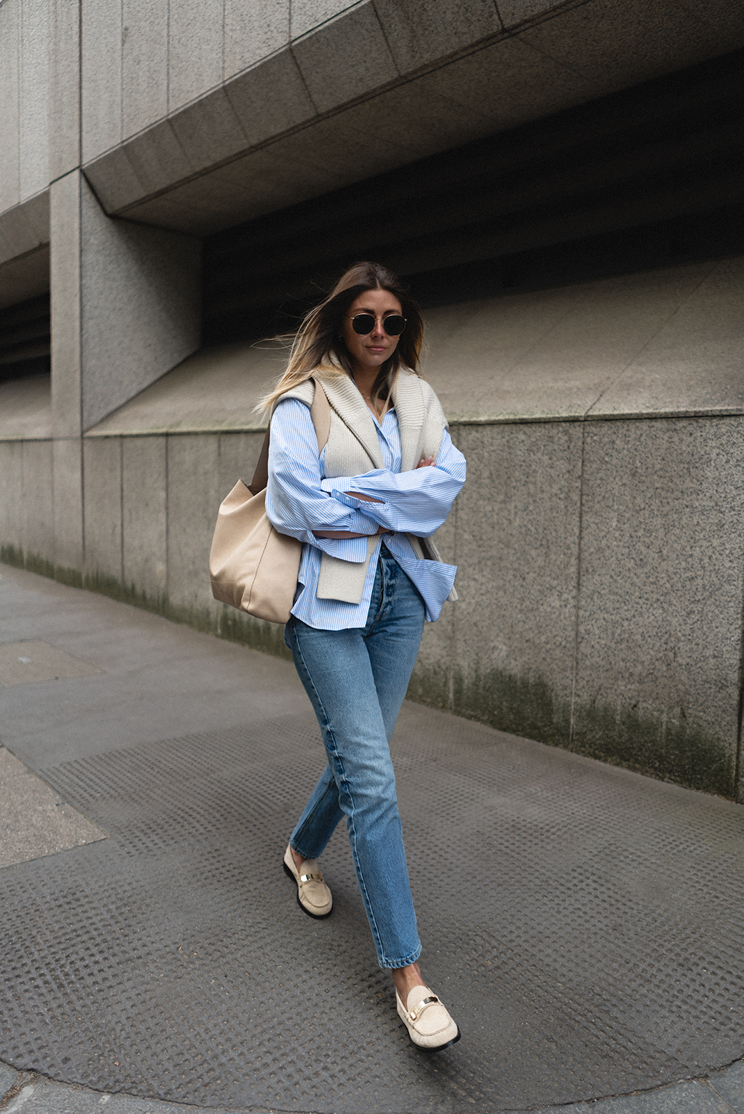 Emma Hill wears blue striped shirt, beige ribbed jumper over shoulders, mid wash straight leg jeans, beige suede loafers. Spring outfit