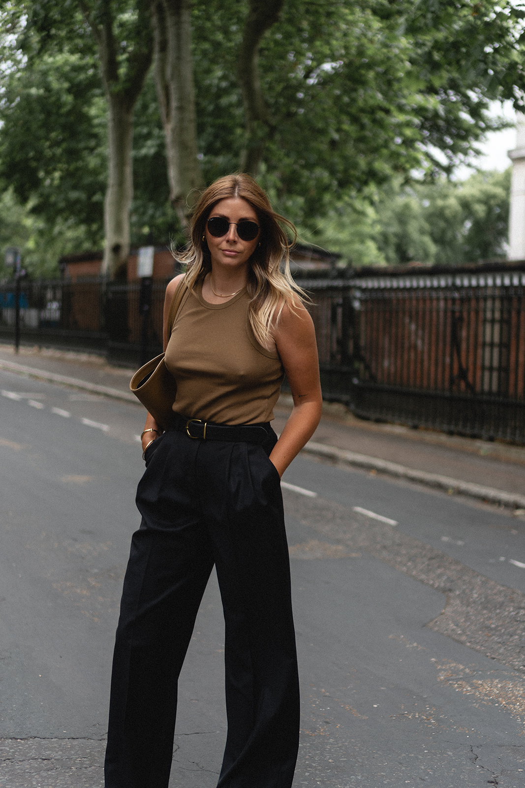 Emma Hill wears green ribbed vest top, Little Liffner tulip tote bag, belted pleated black trousers, Ray-Ban round flat sunglasses.. Chic Summer outfit