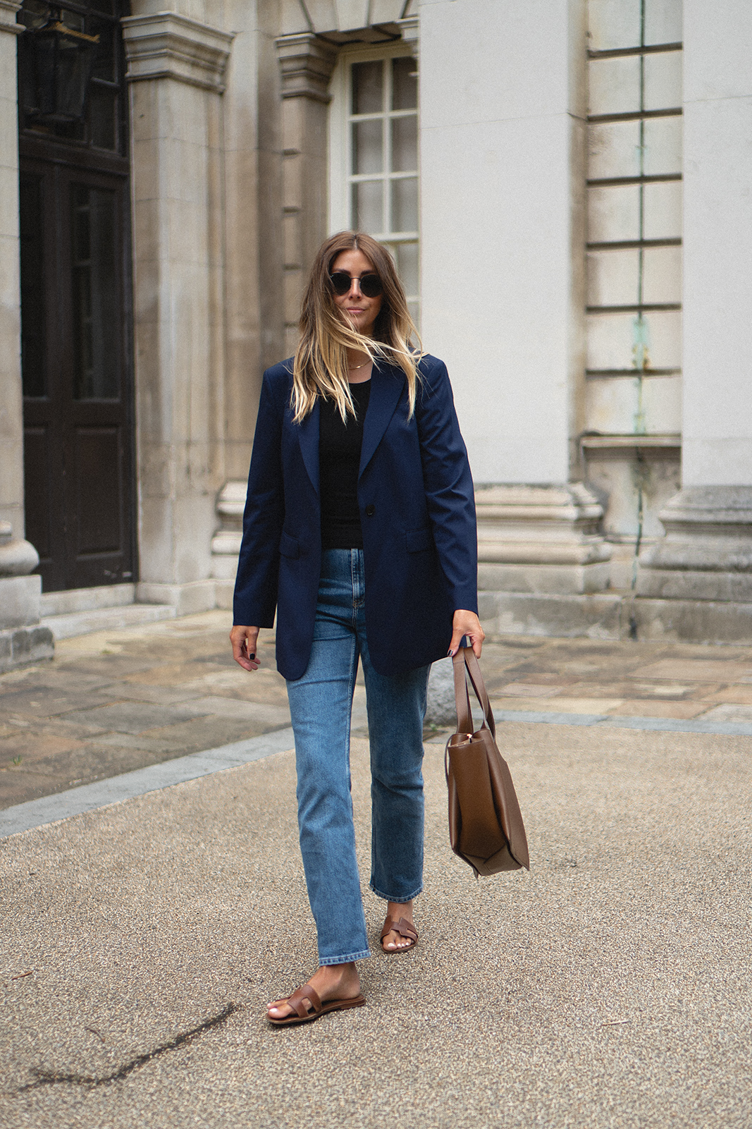 Emma Hill wears navy The Curated x Emma Hill blazer, mid wash straight leg jeans, Hermes Oran sandals, tan leather Celine Tri-Fold bag. Chic Spring Summer outfit
