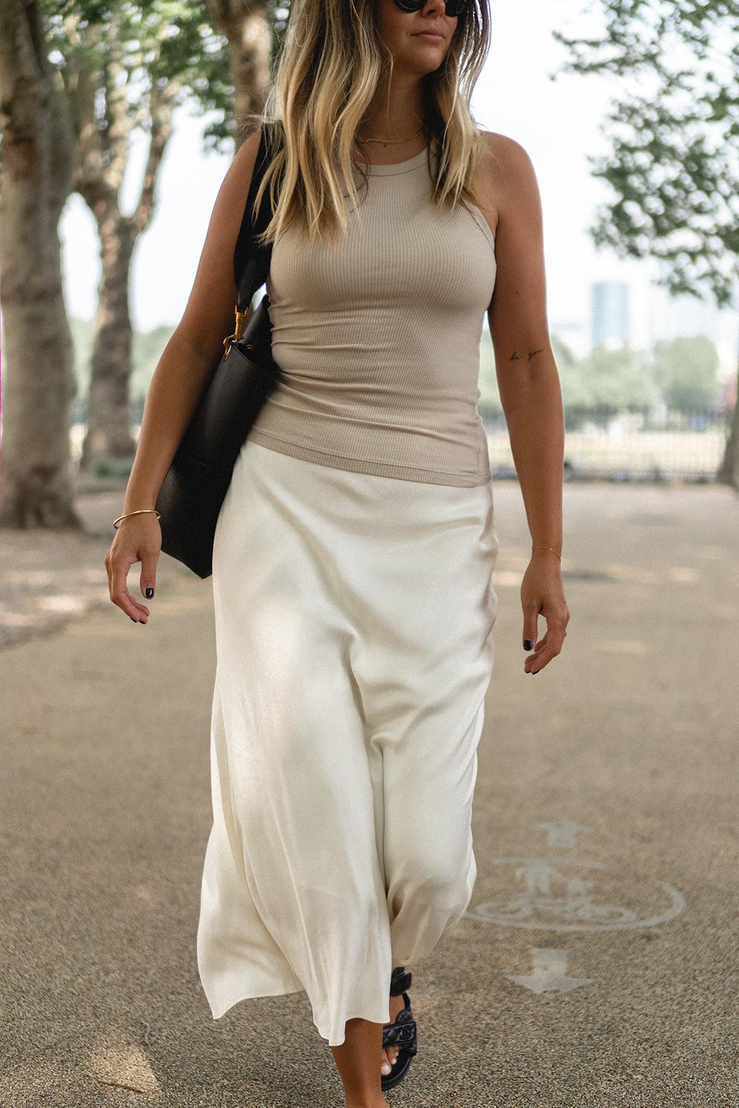 Emma Hill wears white satin slip midi skirt, beige ribbed vest tank top, blac medium Celine Seau Sangle bucket bag, gold jewellery, black nails, chic Summer outfit