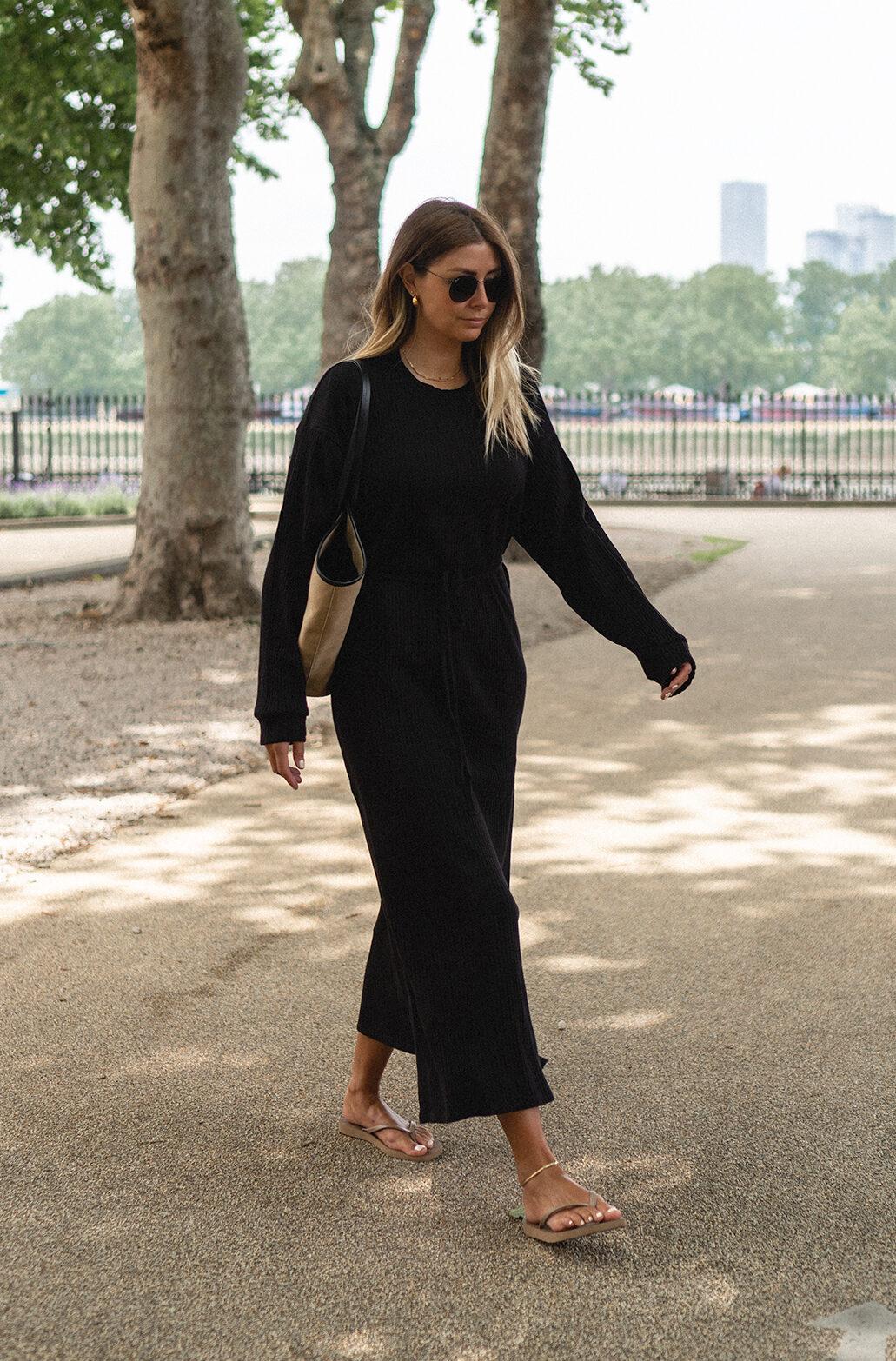 Emma Hill wear Baserange Shaw wrap kaftan dress in black, Sleepers x Envelope 1976 flip flops, beige canvas tote bag