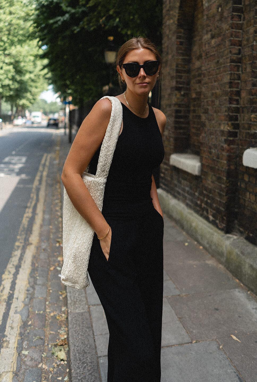Emma Hill wears black crinkle textured trousers, black racerback vest, cream textured oversize shoulder bag. All black outfit