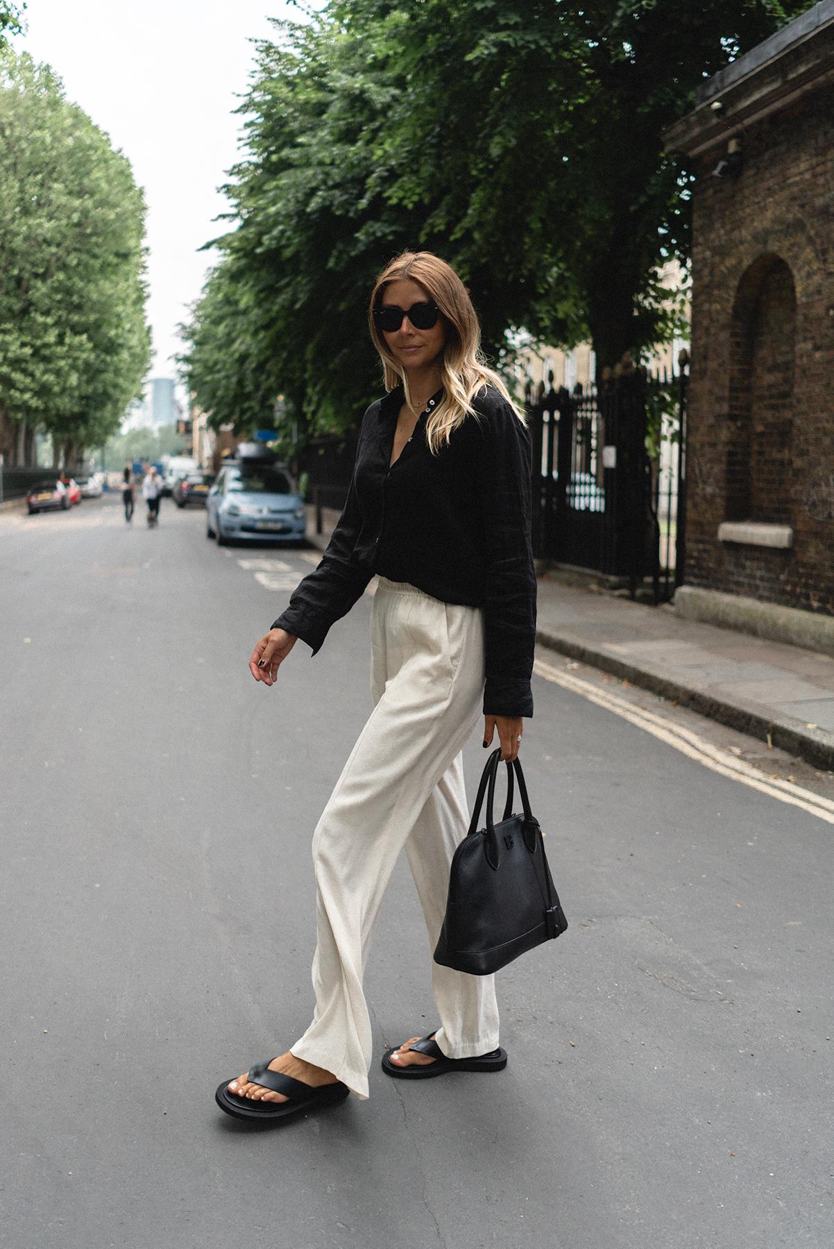 Emma Hill wears black linen shirt, white wide leg trousers, black Dear Frances in sandals, black Balenciaga Ville bag.. Monochrome chic Summer outfit