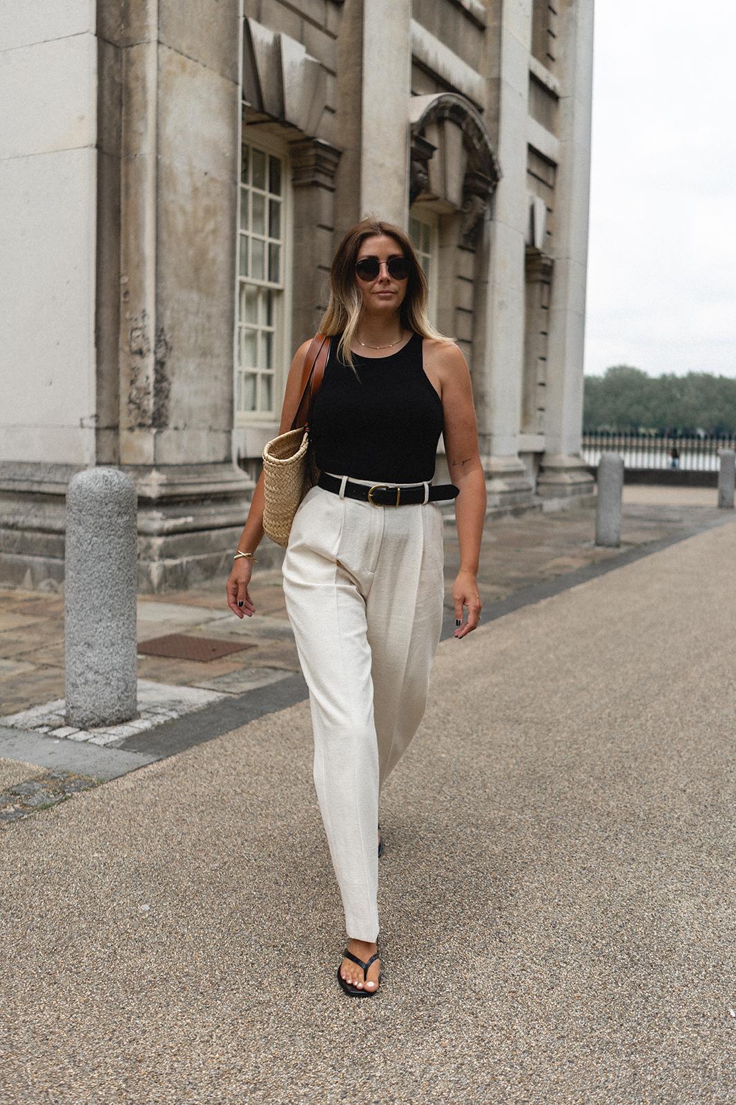 Emma Hill wears black vest tank top, black belt, white linen pleated tailored trousers, black flip flops, Loewe basket bag, black Ray-Ban round sunglasses. Monochrome chic Summer outfit