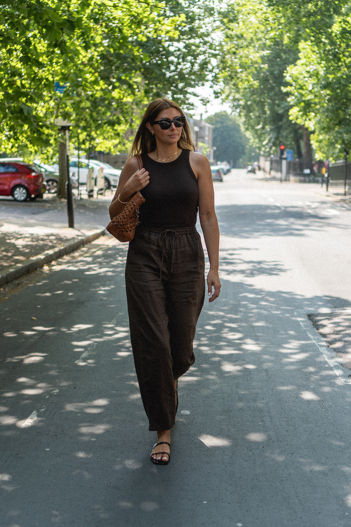 Emma Hill wears brown linen trousers, brown racer back vest top, strappy sandals, Dragon Diffusion Cannage tote bag in tan woven leather. Casual Summer outfit