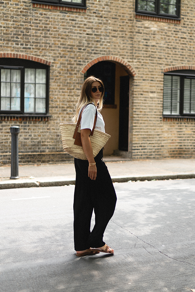 Emma Hill wears medium Loewe basket bag, black satin drawstring wide leg trousers, white oversized t-shirt, tan leather Hermes Oran sandals. Casual but chic Summer outfit