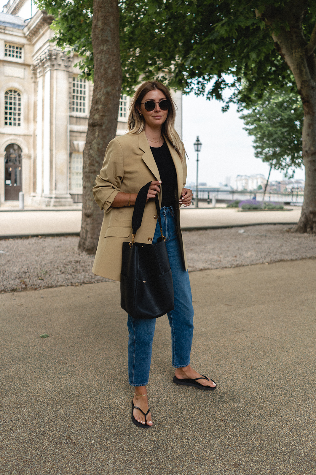 Emma Hill wears vintage yellow blazer, mid wash jeans, blackk Sleepers flip flops, Celine Seau Sangle bag, Ray-Ban round flat sunglasses. Chic Spring Summer outfit