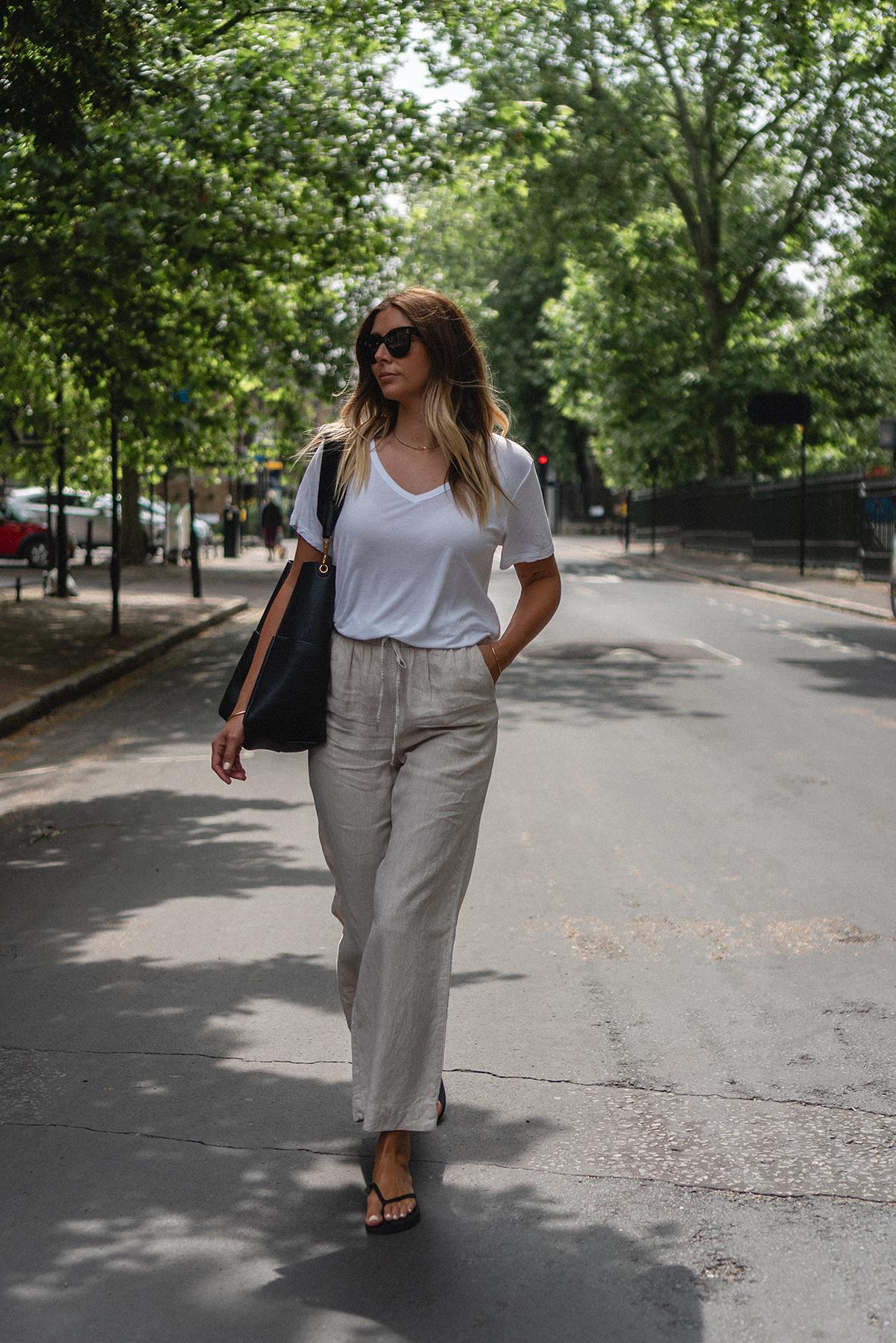 Emma Hill wears white v neck t-shirt, beige linen trousers, Sleepers black flip flops, Celine Seau Sangle bag in black. Casual Summer outfit