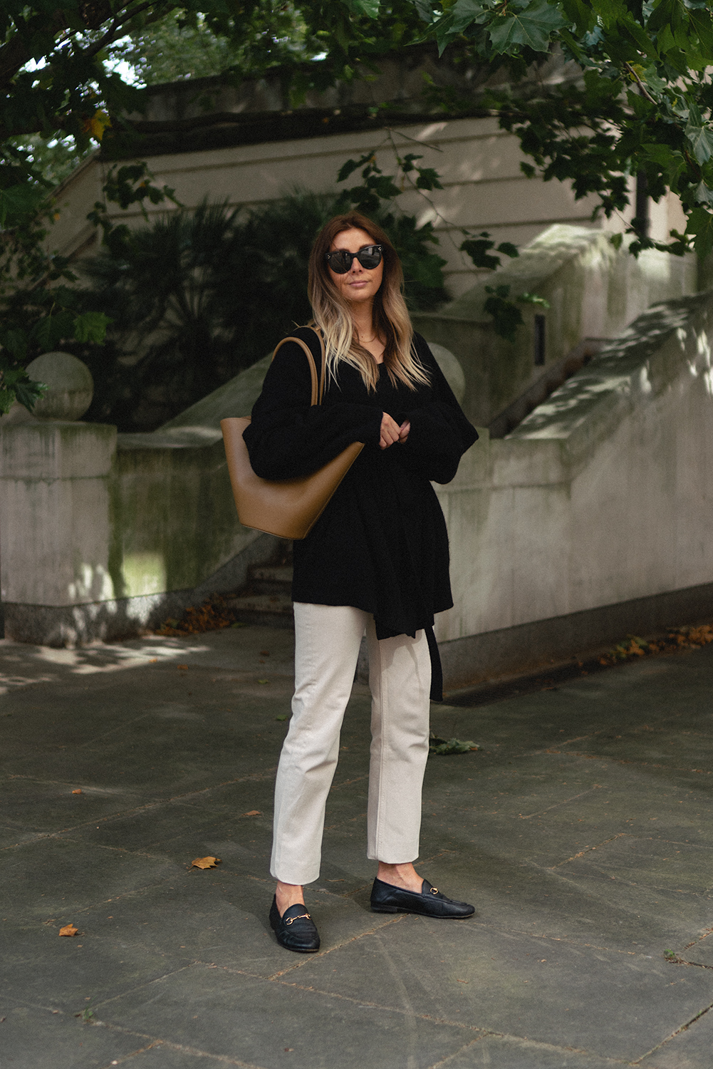 Emma Hill style. Black oversized cashmere wrap belted cardigan, beige jeans, black Gucci Brixton leather horsebit loafers, Little Liffner tulip tote shoulder bag. Autumn outfit