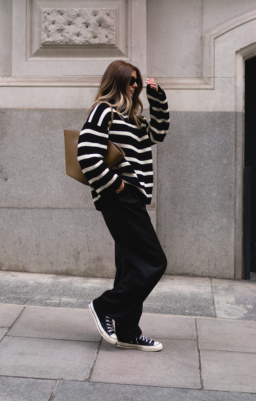 Emma Hill wearing black and white oversized stripe jumper, Celine sunglasses, Little Liffner tall Tulip bag, black tailored wide leg trousers, black Converse high tops . Transitional autumn outfit