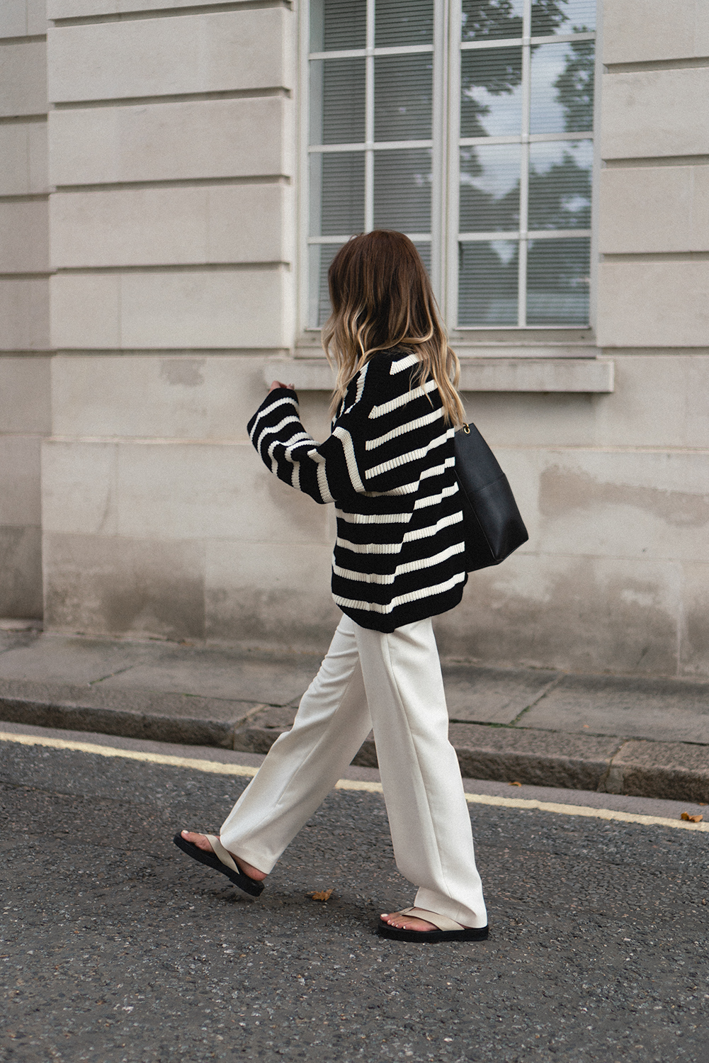 Emma Hill wearing black and white stripe jumper, white wide leg tailored trousers, Celine Seau Sangle bag, thong sandals. Chic transitional outfit Summer to Autumn copy