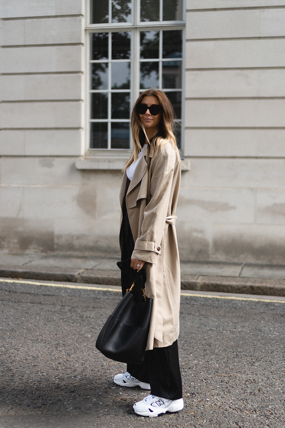 Emma Hill wears beige trench coat, white ribbed cotton vest top, black tailored trousers, New Balance 452 trainers, Celine baby audrey sunglasses, black Celine seau sangle bucket bag. Transitional outfit