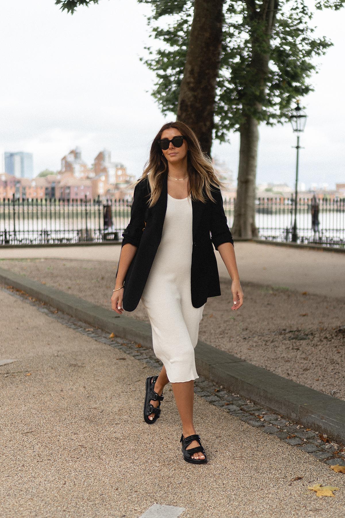 Emma Hill wears cream ribbed midi dress, black classic blazer, Chanel dad sandals, Celine black Seau Sangle bag, Celine Baby Audrey sunglasses. Chic Spring Summer outfit