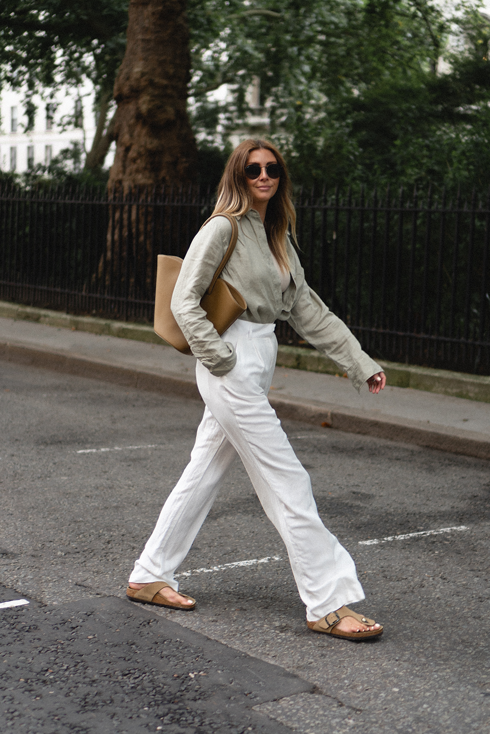 Emma Hill wears sage green linen shirt, beige ribbed vest top, white linen tailored pleated wide leg trousers, Birkenstock Gizeh big buckle sandals, Little Liffner Tulip tote bag. Chic casual Summer outfit