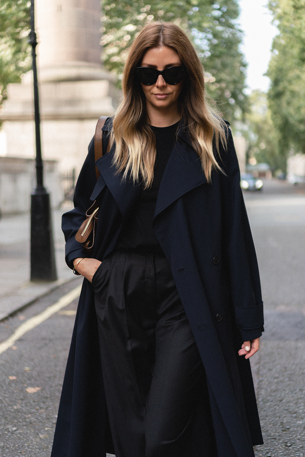 Emma Hill style. Celine Baby Audrey sunglasses, Navy trench coat, black tailored pleated trousers, black t-shirt, Celine Tri-Fold bag in tan leather. Chic Autumn Fall outfit