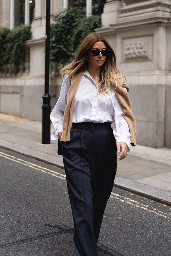 Emma Hill style. White shirt, camel jumper over shoulders, Celine classic bag in camel Leige leather, Ray-Ban State Street sunglases, wide leg navy tailored trousers. Basic minimal Spring Autumn outfit blog
