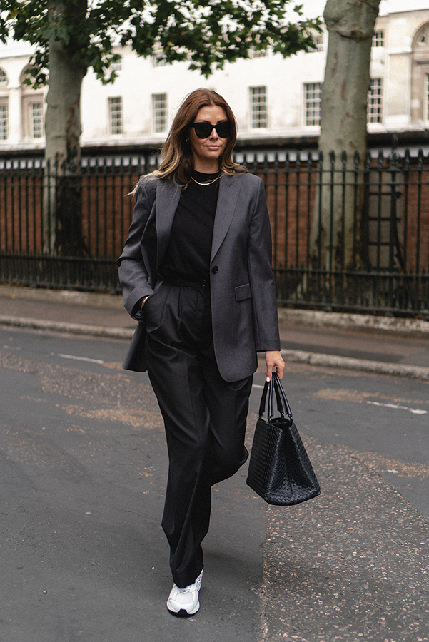Emma Hill wears Celine sunglasses, grey blazer, black t-shirt, black tailored wide leg trousers, Bottega Veneta Intrecciato Milano tote bag, New Balance 2002R trainers, chic casual autumn outfit blog