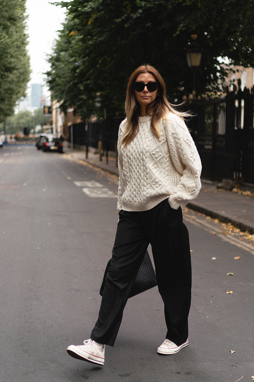 Emma Hill wears LouLou Studios cream aran knit chunky jumper, black tailored trousers, Converse high tops, Celine sunglasses, chic casual Autumn Fall outfit