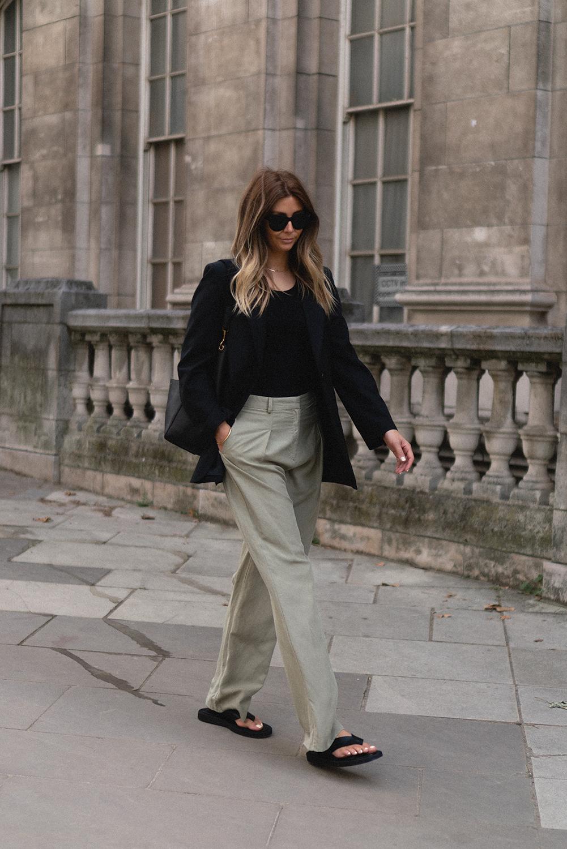 Emma Hill wears black blazer, black vest top, Celine Seau Sangle bag, green wide leg tailored trousers, black leather sandals, Celine sunglasses. Transitional Summer to Autumn outfit copy